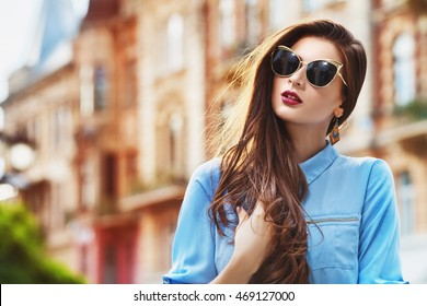 e21dd3a22493 Young woman wearing sunglasses and resting on bench. Outdoor portrait of a  young beautiful confident woman posing on the street. Model wearing stylish