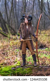 Outdoor portrait of young beautiful demon woman with ram horns, bow and arrows in forest.