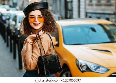Outdoor portrait of young beautiful fahionable happy smiling woman wearing stylish leather beret, orange sunglasses, wrist watch, turtleneck, holding small bag, walking in street of city. Copy space