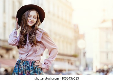 Outdoor portrait of a young beautiful fashionable happywoman posing on a street of the old european city. Model wearing stylish hat, pink blouse, printed skirt. Female fashion concept. Copy space