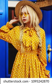 Outdoor portrait of young beautiful fashionable girl wearing trendy yellow color sunglasses, straw hat, polka dot dress posing in street of european city. Blue background. Summer fashion concept