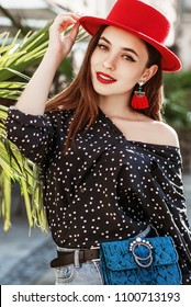 Outdoor portrait of young beautiful fashionable happy smiling girl wearing stylish red hat, earrings, polka dot blouse, blue waist bag posing in street. Summer fashion concept