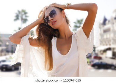 Outdoor portrait of a young beautiful fashionable woman wearing stylish accessories. Hidden eyes with glam glasses. Female fashion, beauty and advertisement concept.Copy space for text.Monaco,palace