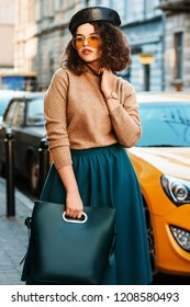Outdoor portrait of young beautiful fashionable woman wearing stylish leather beret, orange aviator sunglasses, wrist watch, cashmere turtleneck, midi skirt, holding green blue bag, posing in street