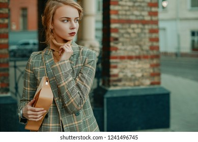 Outdoor portrait of young beautiful fashionable lady wearing stylish checkered blazer, beige cashmere turtleneck, holding small suede bag, posing in street of european city. Copy, empty space for text