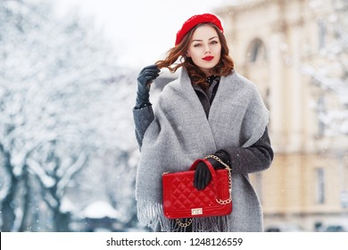 Outdoor portrait of young beautiful  fashionable woman wearing stylish winter gray coat, woolen scarf, red beret, leather gloves, holding quilted bag, posing in street of european city. Copy space