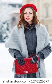Outdoor portrait of young beautiful  fashionable woman wearing stylish winter gray coat, woolen scarf, red beret, black leather gloves, holding quilted bag, posing in street of european city