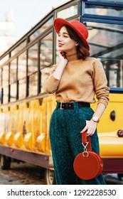 Outdoor portrait of young beautiful fashionable woman wearing orange hat, beige turtleneck, belt, green corduroy trousers, wrist watch, holding round suede handbag, posing in street of european city