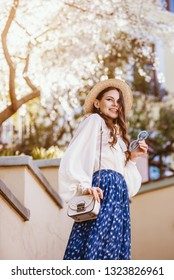 Outdoor portrait of young beautiful fashionable happy smiling woman posing in spring city. Model wearing straw hat, stylish white blouse, blue skirt, carrying small shoulder bag. Sunny day light