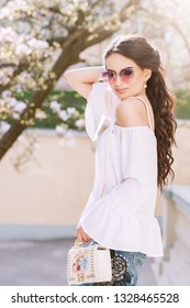 Outdoor portrait of young beautiful fashionable lady wearing white off shoulder blouse, pink sunglasses, holding small bag. Blooming tree on background. Spring, summer fashion concept.