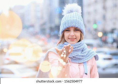Outdoor portrait of young beautiful fashionable happy smiling girl wearing trendy pink coat, blue beanie hat, scarf, posing in street of european city. Winter fashion, Christmas holidays concept