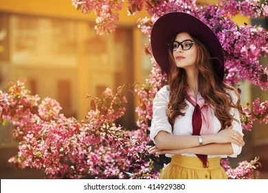 Outdoor portrait of young beautiful fashionable lady posing near flowering tree. Model wearing stylish accessories & clothes. Girl looking aside. Female beauty & fashion. City lifestyle. Copy space