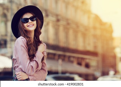 Outdoor portrait of a young beautiful fashionable happy lady posing on a street of the old city. Model wearing stylish clothes. Girl looking up. Female fashion. City lifestyle. Copy space for text