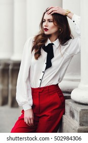 Outdoor portrait of a young beautiful fashionable woman posing on the street. Model looking aside. Lady wearing stylish clothes. Female fashion concept. City lifestyle. Waist up
