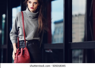 Outdoor portrait of a young beautiful fashionable woman walking on the street, holding red leather bag. Model wearing stylish clothes. Girl looking aside. Female fashion concept. Waist up. Copy space