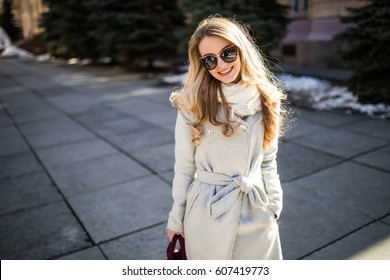 Outdoor portrait of a young beautiful fashionable happy lady posing on a street of the old city. Model wearing stylish clothes. Girl looking up.