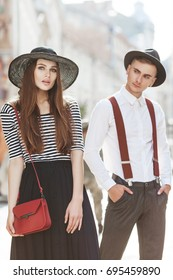 Outdoor portrait of young beautiful fashionable couple. Man and woman posing in street. Guy is out of focus, looks at girl. Models wearing stylish clothes and accessories. Sunny day. Fashion concept