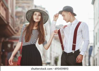 Outdoor portrait of young beautiful fashionable couple. Man and woman posing in street. Girl holding his suspenders. Models wearing stylish clothes and accessories. Sunny day light. Fashion concept