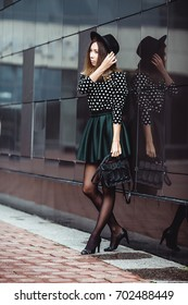 Outdoor portrait of a young beautiful fashionable happy lady posing on a street of the old city. Model wearing stylish clothes. Girl looking up. Female fashion. City lifestyle.