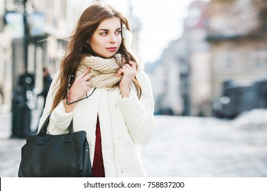 Outdoor portrait of young beautiful fashionable woman wearing stylish white winter puffer coat, scarf, holding leather tote bag. Model walking in street. Female fashion concept. Copy, empty space