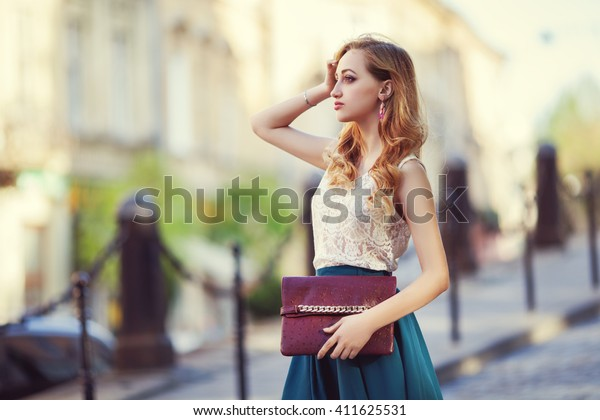 Outdoor portrait of a young beautiful fashionable lady walking posing on a street of the old city. Model wearing stylish clothes. Girl looking aside. Female fashion concept. City lifestyle.