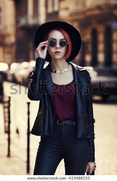 Outdoor portrait of young beautiful fashionable lady posing on the street. Model wearing wide-brimmed hat and stylish leather clothes. Girl looking at camera. Female fashion. City lifestyle