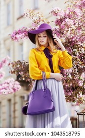 Outdoor portrait of young beautiful girl posing in street with blooming trees, wearing stylish hat, yellow shirt, tulle skirt, holding violet handbag. City lifestyle. Female spring fashion concept
