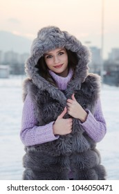 Outdoor portrait of young beautiful girl with long hair wearing hat, sweater posing on a snow ground of European city