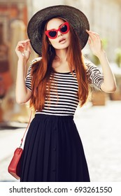 Outdoor portrait of young beautiful girl with long hair posing in street. Model wearing stylish red sunglasses, black hat, stripped blouse, blue skirt. City lifestyle. Sunny day light