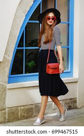 Outdoor portrait of young beautiful girl with long hair walking in street. Model wearing stylish red sunglasses, black hat, striped blouse, dark blue skirt, slippers shoes, has small red bag