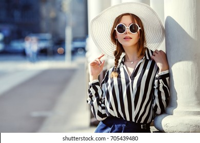 Outdoor portrait of young beautiful girl posing in street. Model wearing stylish sunglasses, hat, stripped black-white blouse. City lifestyle, female fashion concept. Copy, empty space for text