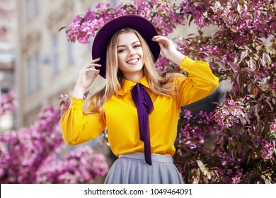 Outdoor portrait of young beautiful happy smiling girl posing in spring street with blooming pink trees. Model wearing stylish violet hat, bow tie, yellow blouse, skirt. Female fashion concept