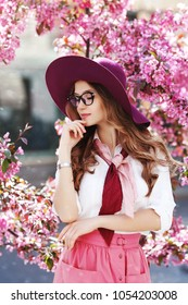 Outdoor portrait of young beautiful happy smiling girl posing in street, near blooming tree. Model wearing stylish hat, glasses, pink scarf, skirt, white shirt. Female fashion concept
