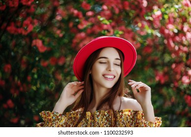 Outdoor portrait of young beautiful happy smiling girl with healthy white teeth, radiant clean skin, long hair, wearing red hat, yellow blouse, posing in flowering garden. Summer fashion concept