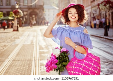 Outdoor portrait of young beautiful happy smiling woman wearing stylish striped dress, hat, holding bright pink straw bag with peonies, posing in street of european city. Summer fashion. Copy space