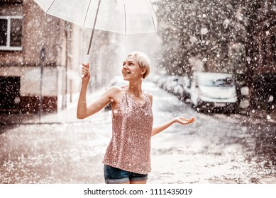 Outdoor portrait of young beautiful happy smiling girl holding transparent umbrella, posing under rain in street of european city