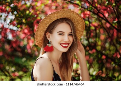 Outdoor portrait of young beautiful happy smiling girl with red lips, long hair, wearing straw hat, long tassel earrings, cold shoulder dress, posing naer blooming tree. Copy, empty space for text
