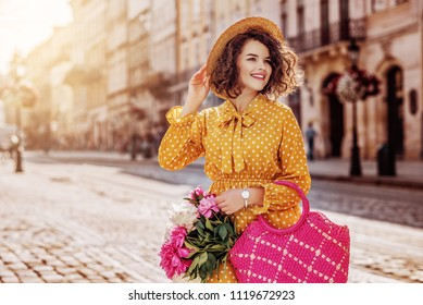 Outdoor portrait of young beautiful happy smiling girl wearing yellow polka dot dress, hat, holding straw bag with peonies, posing in street of european city. Spring, summer fashion. Copy space