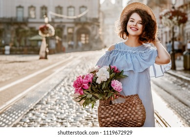 Outdoor portrait of young beautiful happy smiling woman posing in street of european city. Model wearing striped dress, holding straw bag with peonies. Copy, empty space for text
