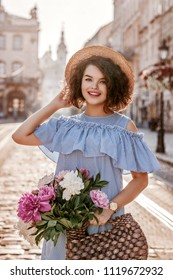 Outdoor portrait of young beautiful happy smiling woman wearing hat, striped dress, holding straw bag with peonies, posing in street of european city. Female spring, summer fashion concept
