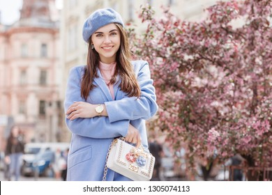 Outdoor portrait of young beautiful happy smiling fashionable woman wearing spring coat, beret, wrist watch, holding white bag with flowers application, posing in street of European city. Copy space