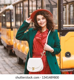 Outdoor portrait of young beautiful happy smiling lady wearing orange hat, snakeskin printed dress, green coat, with white cross body bag, posing in street of European city
