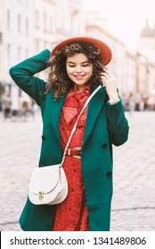 Outdoor portrait of young beautiful happy smiling lady wearing orange hat, dress, green coat, with white cross body bag walking in street of European city