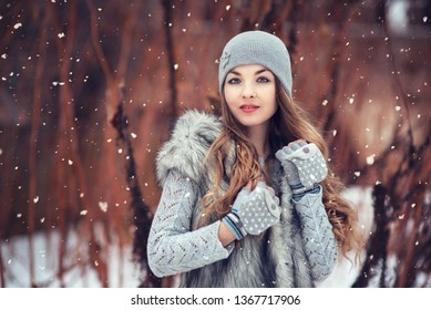 Outdoor portrait of young beautiful happy smiling girl. Magic snowfall. Christmas, new year, winter holidays concept. City lifestyle