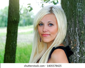 Outdoor portrait of young beautiful happy smiling lady with blondie hair posing near tree. Girl open her eyes. Female beauty & fashion concept.