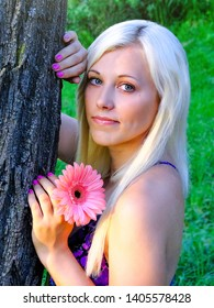 Outdoor portrait of young beautiful happy smiling lady with blondie hair posing near tree. Girl open her eyes. Female beauty & fashion concept. Girl holding a pink gerbera in his hand.