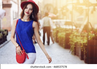 Outdoor portrait of young beautiful happy smiling woman posing on street. Model wearing stylish hat and clothes. Girl looking at camera. Female fashion. Sunny day. City lifestyle. Copy space for text