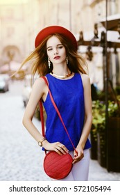 Outdoor portrait of young beautiful happy smiling woman walking on street. Model wearing stylish hat, clothes, has round quilted bag. Girl looking at camera. Female fashion. Sunny day. City lifestyle