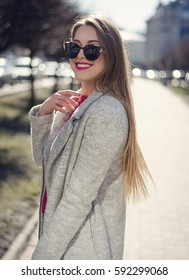 Outdoor portrait of a young beautiful happy smiling woman with long hair posing on the street wearing coat with sunglasses, looking at the camera.