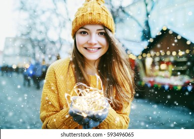 Outdoor portrait of young beautiful happy smiling hipster girl posing on street, looking at camera, holding festive garland. Model wearing stylish winter yellow hat, sweater. Snowfall. City lifestyle